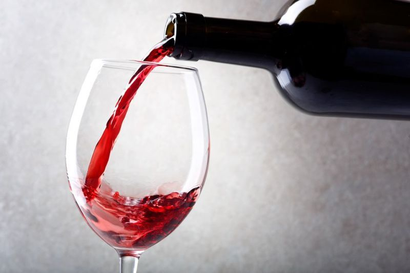 red-wine-is-poured-into-a-glass-from-a-bottle-light-background-1153158143-98320451802c485cb6d7b5437c7fd60a
